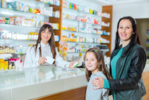 pharmacist and adult woman with her daughter in the drugstore